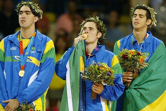 Ricardinho (ao centro) beija medalha de ouro em Atenas-2004, ao lado de Rodrigão e Dante (Flávio Florido - 29.ago.04/Folhapress)