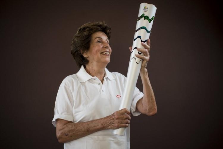 A ex-tenista Maria Esther Bueno, 75, uma das condutoras em SP, exibe a tocha olímpica em visita à redação da Folha (Fábio Braga/Folhapress)