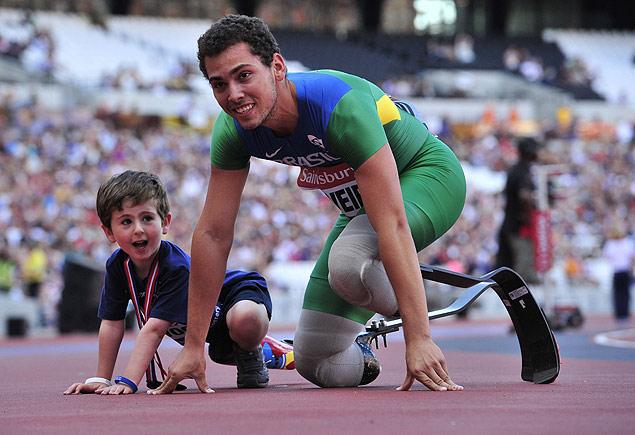 O brasileiro Alan Fonteles, 20, posa com o britânico Rio Woolfe, 5, vítima de meningite, no Estádio Olímpico de Londres (Glyn Kirk/AFP)