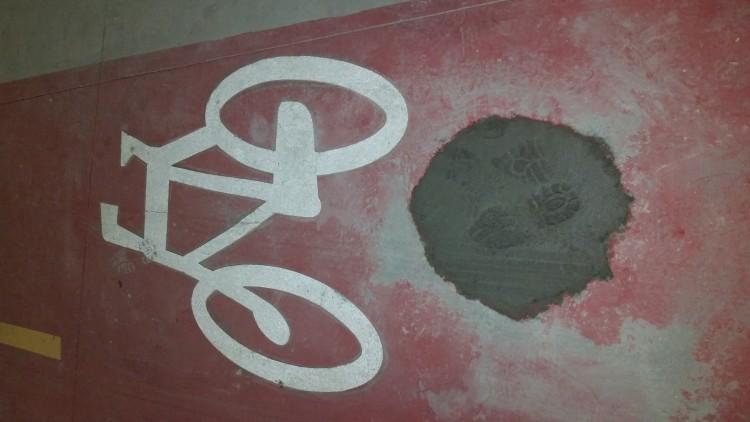 Detalhe do buraco tapado, onde havia o poste na ciclovia do Parque Olímpico (Marcel Merguizo/Folhapress)
